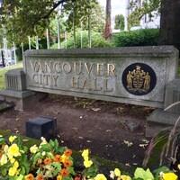 L'enseigne en béton de l'hôtel de ville de Vancouver dans un parterre de fleurs.
