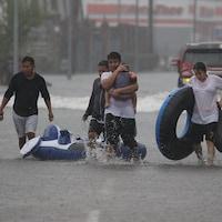 Un groupe de sinistrés marchent dans une rue inondée.