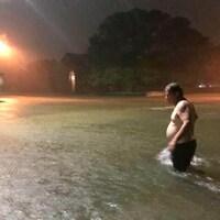 Un homme du secteur Clear Lake de Houston au Texas se promène dans la rue inondée de son quartier.