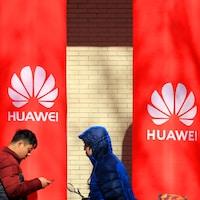 Des gens marchent à côté de poteaux ornés de logos de Huawei.