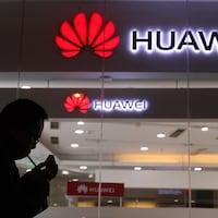 Un homme fume une cigarette devant l'entrée d'un magasin Huawei.