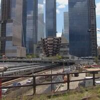 La sculpture et des gratte-ciel près d'une gare avec des trains.
