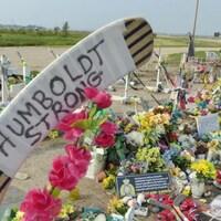 Un avant-plan sur un bâton de hockey avec les mots « Humboldt Strong » inscrits sur le ruban de la palette. Derrière, on voit des dizaines de fleurs de toutes les couleurs ainsi que d'autres objets pour commémorer les morts.