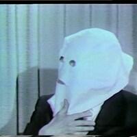 Igor Gouzenko, le visage camouflé par une large cagoule blanche.