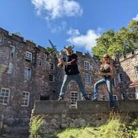Un couple avec des fausses épées et des casques vikings font la pose devant un petit château de pierre.