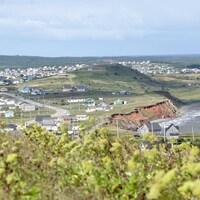 Une partie des Îles-de-la-Madeleine vue de haut. Des maisons se dressent sur le bord d'une falaise.