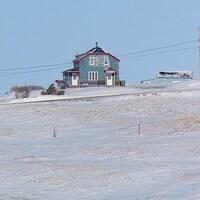 Des maisons enneigées sur une butte des Îles-de-la-Madeleine.