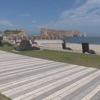 Des touristes sont assis sur des chaises longues ou se promènent sur une plage devant le Rocher-Percé.