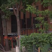 L'immeuble où Pierre Coriolan, un homme en crise, a été abattu par le SPVM, dans le quartier Centre-Sud, à Montréal, avec un ruban policier devant une entrée.