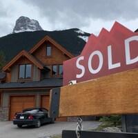 """Un panneau """"vendu"""" devant une maison de Canmore."""