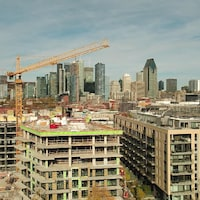 Une grue surplombe un immeuble en construction.