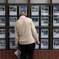 Une personne de dos regarde des maisons à vendre.