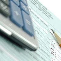 Une calculatrice et un crayon sont posés sur un formulaire de déclaration de revenus.