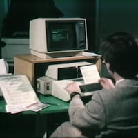 Homme, de dos, qui travaille avec un ordinateur à l'allure ancienne.