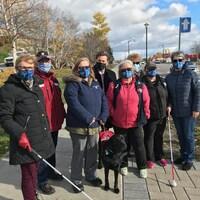 Un regroupement de personne se trouvent avec le maire Yves Montigny, ainsi qu'un chien, juste à côté du feux de circulation sur le Boulevard Lasalle à Baie-Comeau.