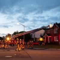 Une quinzaine de pompiers devant une maison endommagée par les flammes, avec l'échelle d'un camion déployé vers la toiture.