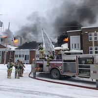 Les pompiers tentent d'éteindre les flammes qui s'échappent de la bâtisse.
