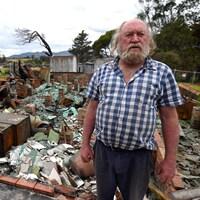 Un homme âgé se tient debout devant les ruines de sa maison.