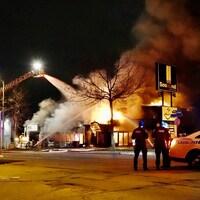 Les flammes font rage dans un bâtiment commercial de Laval. Les pompiers tentent de combattre les flammes.