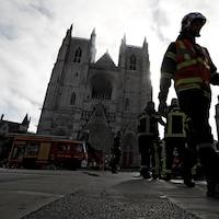Plusieurs pompiers et camions sur la place devant la cathédrale de Nantes.