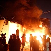 Des manifestants devant un édifice en flammes.