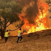 Deux hommes près d'un grand feu de broussailles.