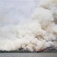 Un feu de forêt près d'un lac.