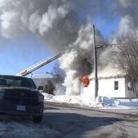Des flammes s'échappent de la fenêtre de la résidence et on voit la fumée qui monte dans le ciel.