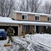Des pompiers sur les lieux de l'incendie au croissant Buchanan.