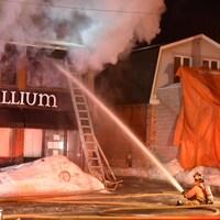 Un pompier est assis au sol alors qu'il tente d'éteindre un feu.