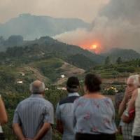 Des habitants de l'île de Grande Canarie, près de Montana Alta, observent la fumée d'un incendie de forêt qui fait rage, 18 août 2019.