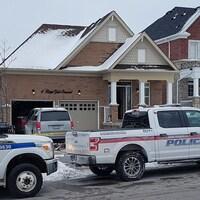 Des véhicules d'urgence stationnés devant une maison