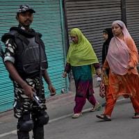 Des femmes musulmanes passent derrière un militaire tenant sa carabine dans une rue où les commerces sont fermés.