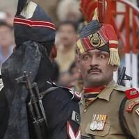 Un militaire indien (de face) toise un militaire pakistanais (de dos).