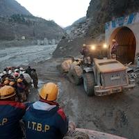 Des membres de la police des frontières indo-tibétaine regardent comment une machine est utilisée pour dégager un tunnel après la rupture d'une partie d'un glacier, à Tapovan.