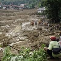 Sur une grande surface boueuse, des secouristes cherchent des rescapés.
