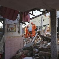 Des sauveteurs dans une maison détruite.
