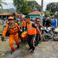 Dans un village où certaines maisons sont détruites, des secouristes transportent un corps dans un sac, entourés de badauds.