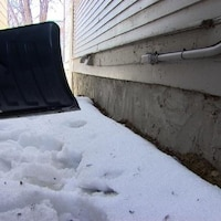 Une pelle près de la fondation d'une maison d'où l'on enlève de la neige.