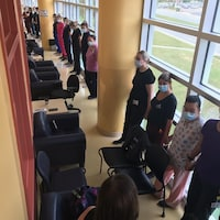 Des infirmiers masqués, debout dans un corridor en signe de protestation.