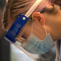 Une infirmière penche la tête vers l'avant pour discuter avec un patient.