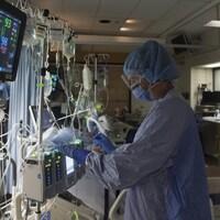 Une infirmière dans un hôpital, à côté d'un patient sous aide respiratoire.