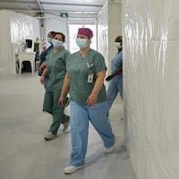 Quatre infirmières masquées marchent dans un corridor.