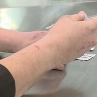 Gros plan sur des mains utilisant une seringues pour s'injecter de la drogue.