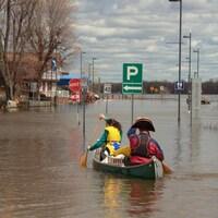 Un homme et une femme en canot à travers les rues inondées