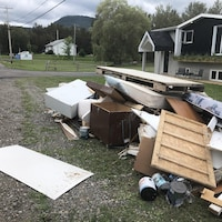 Des débris jonchent le sol devant une maison.