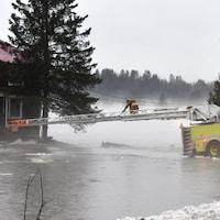 Un pompier sur une échelle s'avance vers une maison inondée