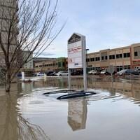Une voiture sous l'eau pendant des inondations dans un centre-ville.