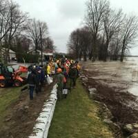 Des gens travaillent à renforcer une digue près de l'eau.