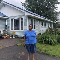 une femme se tient fièrement devant sa maison